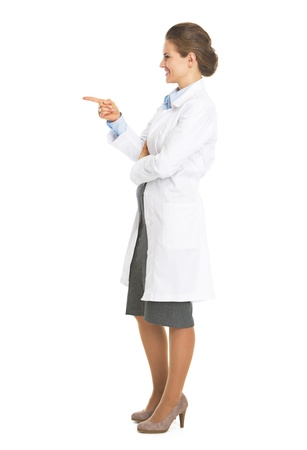 Full length portrait of smiling doctor woman pointing on copy space Stock Photo - 21511439