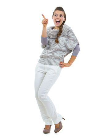 Full length portrait of happy young woman in sweater pointing on copy space Stock Photo - 21792257