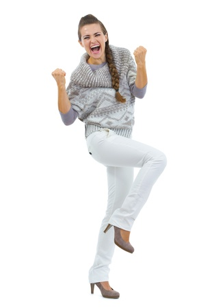Full length portrait of happy young woman in sweater making fist pump gesture photo