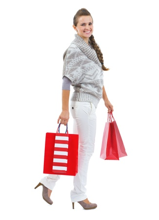 Full length portrait of smiling young woman in sweater with christmas shopping bags Stock Photo - 21792283