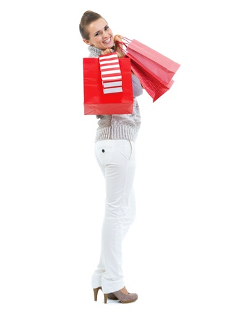 Full length portrait of happy young woman in sweater holding christmas shopping bags photo