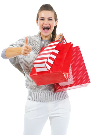 Surprised young woman in sweater with shopping bags showing thumbs up Stock Photo - 21792299