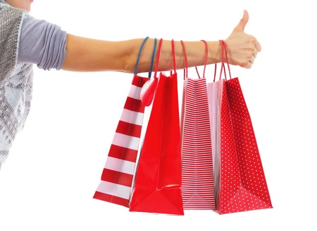 Closeup on young woman hand with christmas shopping bags showing thumbs up Stock Photo - 21792301