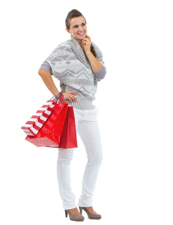 Full length portrait of thoughtful young woman in sweater with shopping bags Stock Photo - 21792302