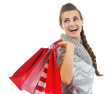 Happy young woman in sweater with christmas shopping bags looking on copy space Stock Photo - 21792303