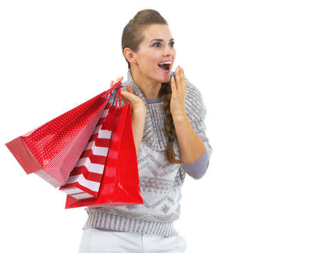 Surprised young woman in sweater with christmas shopping bags looking on copy space Stock Photo - 21792304
