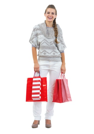 Full length portrait of happy young woman in sweater holding christmas shopping bags Stock Photo - 21792305