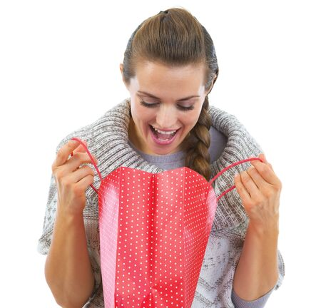 Happy young woman in sweater looking in christmas shopping bag Stock Photo - 21792306
