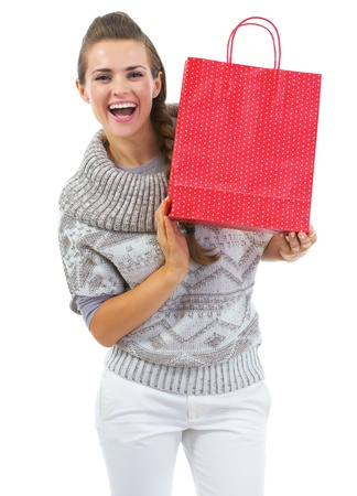 Smiling young woman in sweater showing christmas shopping bag Stock Photo - 21792307
