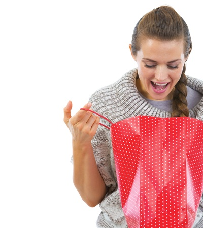 Closeup on happy young woman in sweater looking in christmas shopping bag photo