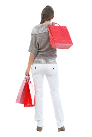 Full length portrait of young woman in sweater holding christmas shopping bags . rear view Stock Photo - 21792309