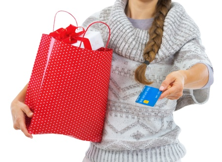 Closeup on credit card in hand of young woman in sweater with christmas shopping bag photo