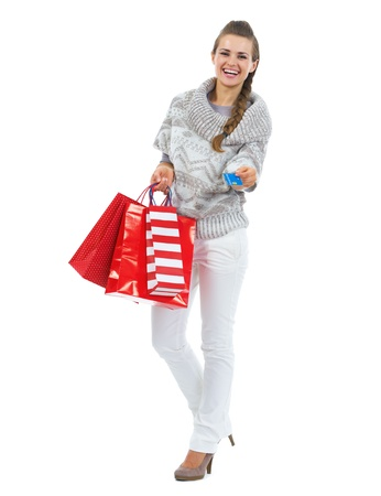 Full length portrait of smiling young woman in sweater with christmas shopping bag giving credit card Stock Photo - 21792315