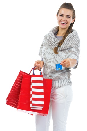 Smiling young woman in sweater with christmas shopping bag giving credit card Stock Photo - 21792319