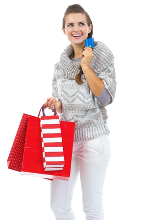 Thoughtful young woman in sweater with christmas shopping bag and credit card Stock Photo - 21792320