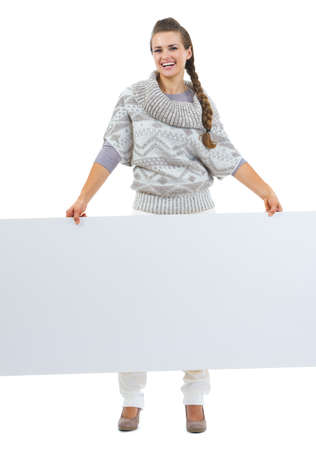 Full length portrait of smiling young woman in sweater holding blank billboard photo