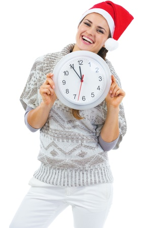 Smiling young woman in sweater and christmas hat showing clock Stock Photo - 21792332