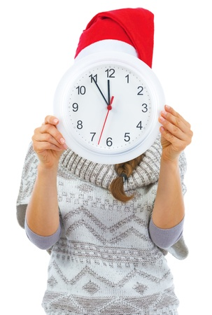 Young woman in sweater and christmas hat hiding behind clock Stock Photo - 21792333