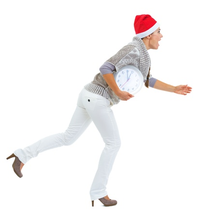 Shocked young woman in sweater and christmas hat running with clock Stock Photo - 21792334