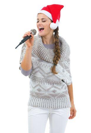 cappello natale: Felice giovane donna in maglione e cappello di natale che canta in microfono