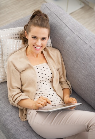 divan: Smiling young woman sitting on divan and using tablet pc