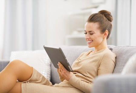 Happy young woman sitting on couch and working on tablet pc photo