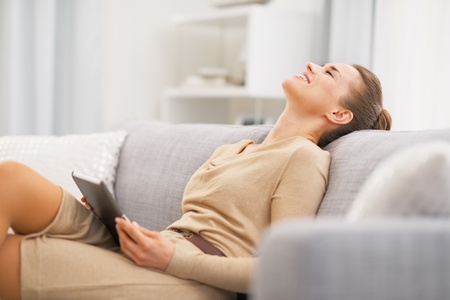 Relaxed young woman sitting on sofa with tablet pc Stock Photo