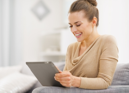 Smiling young woman sitting on couch and working on tablet pc Stock Photo - 21792396