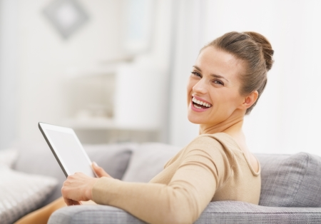 topicality: Smiling young woman with tablet pc sitting on sofa