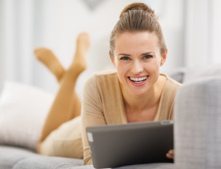 topicality: Smiling young woman with tablet pc laying on sofa