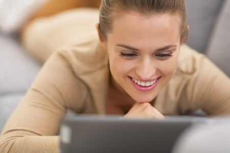 Happy young woman with tablet pc laying on couch Stock Photo - 21792401