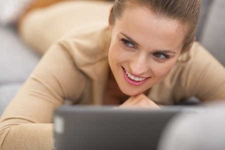topicality: Thoughtful young woman with tablet pc laying on couch Stock Photo