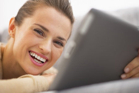 Smiling young woman with tablet pc laying on sofa Stock Photo - 21792433