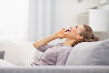 Happy young woman talking mobile phone while relaxing on couch Stock Photo - 21792403