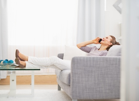 Happy young woman talking cell phone while sitting on sofa Stock Photo - 21792405
