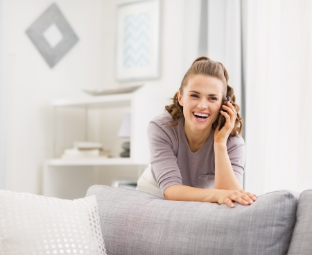 Happy young woman talking cell phone in living room Stock Photo - 21792406