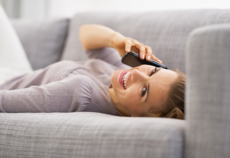 Smiling young woman talking mobile phone while laying on couch Stock Photo - 21792440