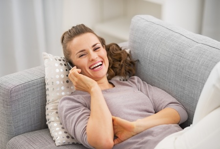 Smiling young woman talking mobile phone while laying on couch photo