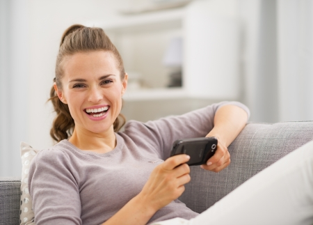 Smiling young woman reading sms while sitting on sofa Stock Photo - 21792447