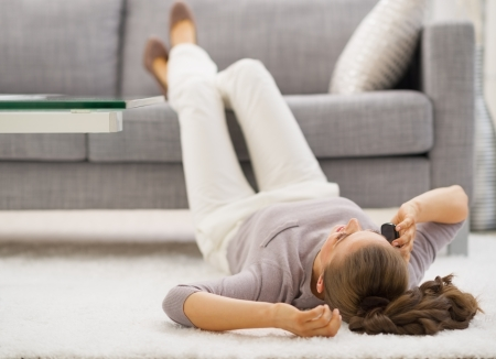 Young woman talking mobile phone while laying on floor Stock Photo - 21792453