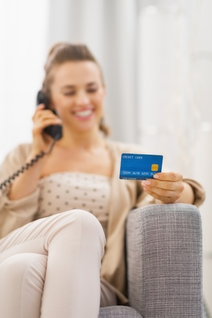 Closeup on credit card in hand of young woman talking phone Stock Photo - 21792477