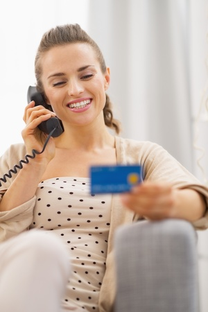 Happy young woman with credit card talking phone while sitting on sofa Stock Photo - 21792479