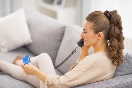 Young woman with credit card talking phone while laying on sofa . rear view photo