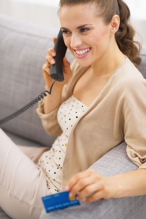Smiling young woman with credit card talking phone while sitting on sofa Stock Photo - 21792481