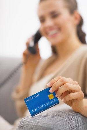 Closeup on credit card in hand of young woman talking phone Stock Photo - 21792482