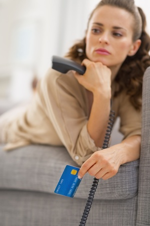 disquieted: Closeup on credit card in hand of concerned young woman with phone Stock Photo