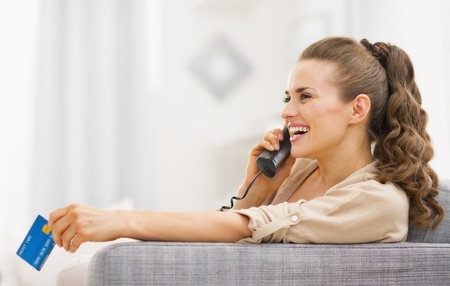 Happy young woman with credit card talking phone in living room Stock Photo - 21792485