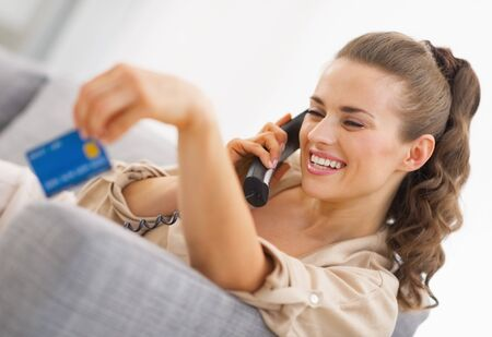 playing on divan: Happy young woman playing with credit card while talking phone Stock Photo