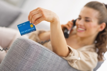 Closeup on credit card in hand of young woman talking phone Stock Photo - 21792487