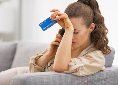 Frustrated young woman with credit card and talking phone Stock Photo - 21792489